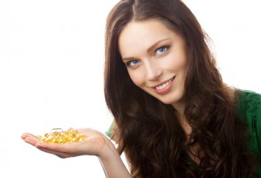 Portrait of woman showing Omega 3 fish oil capsules, isolated on