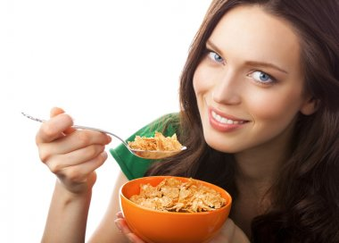 Portrait of young smiling woman eating muesli or cornflakes, iso