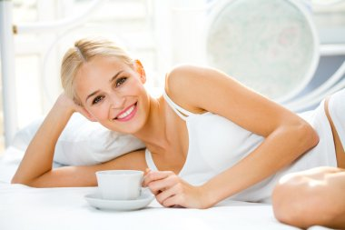 Portrait of beautiful woman with cup on bed at bedroom
