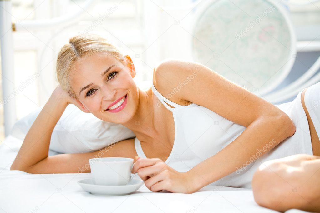 Porträt einer schönen Frau mit Tasse auf dem Bett im