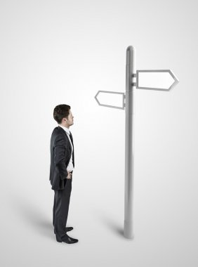 Businessman standing at a crossroad