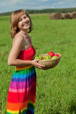 Smiling girl with a basket of apples