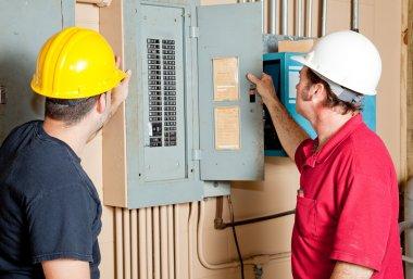 Repairmen Examine Electrical Panel