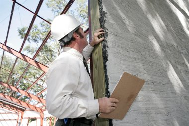 A building inspector checking over incomplete stucco work on new construction. Focus on stucco work. stock vector