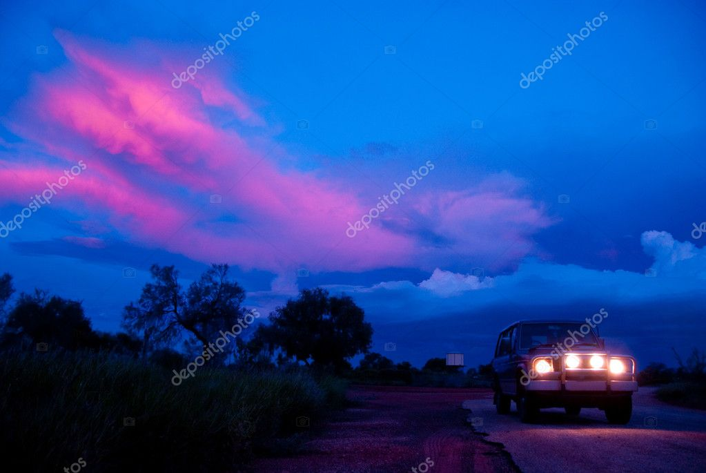 Headlamps Of Car In Dark With Colorful Sky