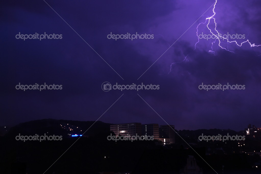 Lightening During Night With Visible Sillhuettes Of Buildings