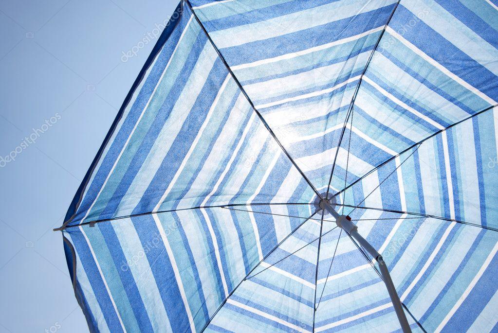 Blue Backlit Parasol Against Plain Sky