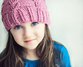 Fotografie rozkošný usmívající se dívka dítě v růžový pletený klobouk