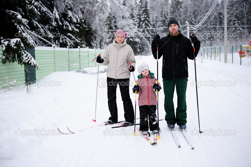 Young parents and their daughter do Nordic skiing