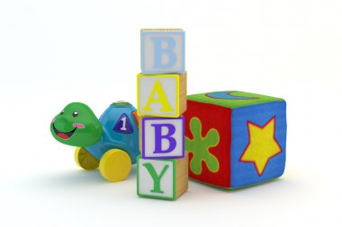 Wood toy blocks spelling baby with baby toys in background