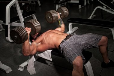 Male bodybuilder working out in a gym.
