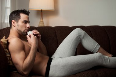 Attractive man relaxing at home in long underwear.