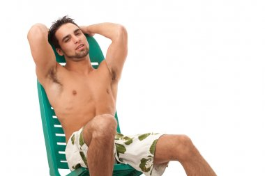 Attractive young man in boardshorts. Studio shot over white.