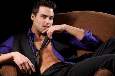 Well dressed man in chair, shirt open. Studio shot over black.