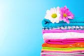 hromadu barevných šatů a květin na modrém pozadí