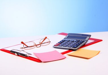 Glasses, calculator and paper on table