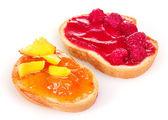 Fotografia delizioso pane tostato con marmellata e frutta isolato su bianco