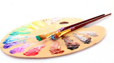 Wooden art palette with blobs of paint and a brush on white back