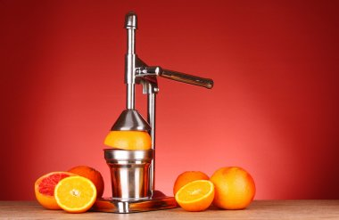 Juicer and oranges on red background