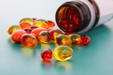 Red and yellow capsules of vitamins on a blue background