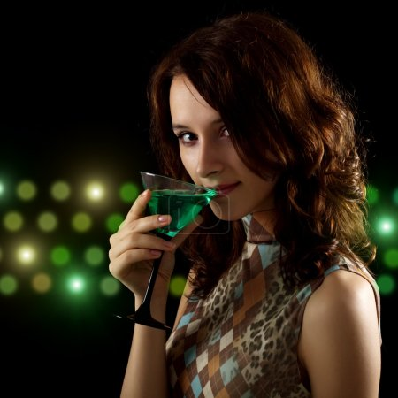 Photo for Young woman with a green cocktail on a black background - Royalty Free Image