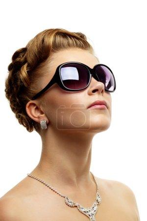 Young stylish woman wearing sunglasses on white