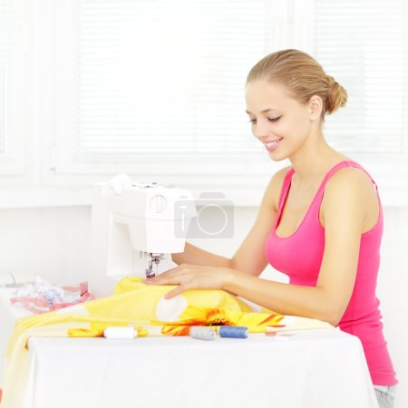 Girl using sewing machine to sew clothing
