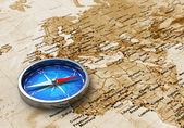Bussola metallo blu sulla mappa del mondo antico