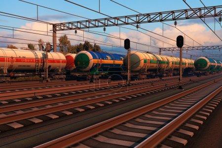 Trenes de mercancías con vehículos cisterna de combustible al atardecer