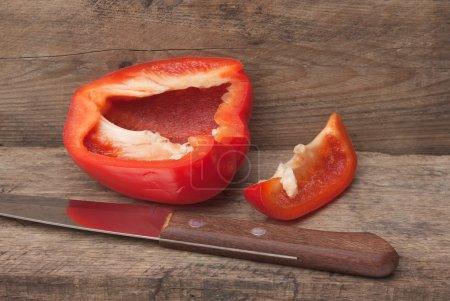 Foto de Rodajas pimiento rojo búlgara y el cuchillo sobre un fondo de madera - Imagen libre de derechos