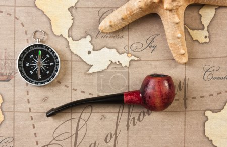 Tobacco pipe and compass on map