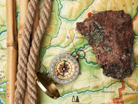 Photo for Compass with a rope and a stone on a topographic map - Royalty Free Image