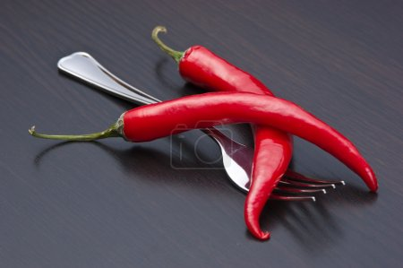 Red chili peppers and fork on the kitchen table