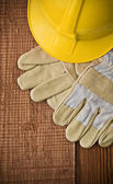 View on a hardhat with gloves on wooden board