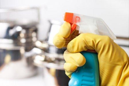 Photo pour Main dans le gant de protection tenant pulvérisation. nettoyage d'un concept de cuisine - image libre de droit