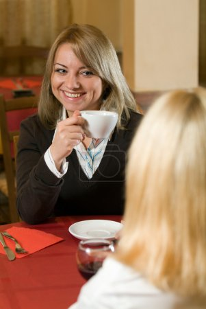 A young businesswoman in a cafe with a cup in her hand