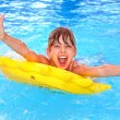 Children sitting on inflatable ring in swimming po...