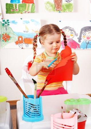 Photo pour Enfant avec ciseaux papier découpé dans la salle de jeux. Préscolaire . - image libre de droit