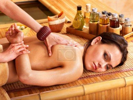 Photo pour Jeune femme se faire masser dans un spa en bambou . - image libre de droit
