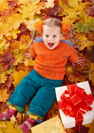 Child in autumn orange leaves and gift box.