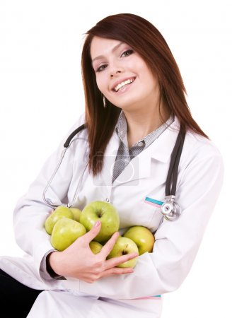 Doctor with stethoscope and group green apples.