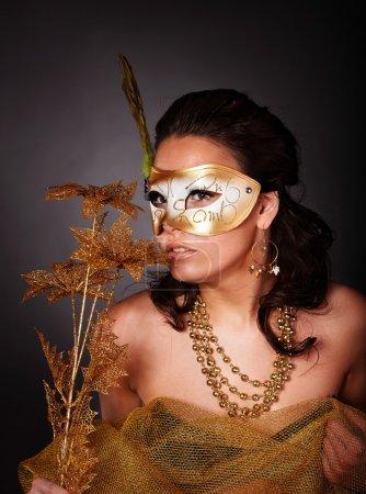 Photo pour Belle jeune femme avec masque doré et fleur sur fond gris . - image libre de droit