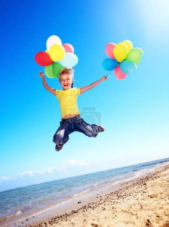 Photo for Little girl playing with balloons at the beach. - Royalty Free Image