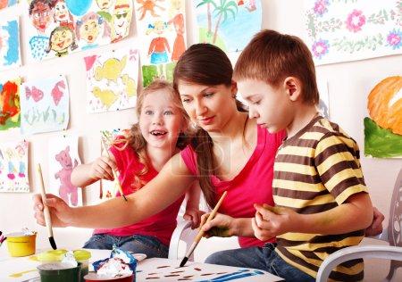 Foto de Los niños con el maestro dibujan pinturas en la sala de juegos. cuidado de niños. - Imagen libre de derechos