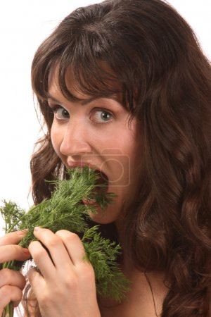 Photo for Woman eating dill. Healthy eating. - Royalty Free Image