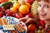 enfant avec fruits et vitamine pilule