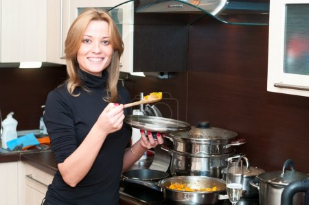 Beautiful happy smiling woman in kitchen interior with food in pan.