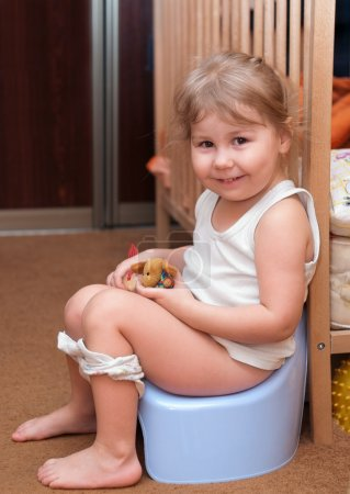 Photo for Little Caucasian girl sitting on a chamber pot in the room - Royalty Free Image