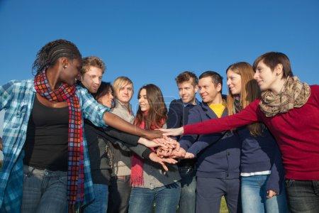 Photo pour Étudiants heureux avec les mains sur la pile - image libre de droit