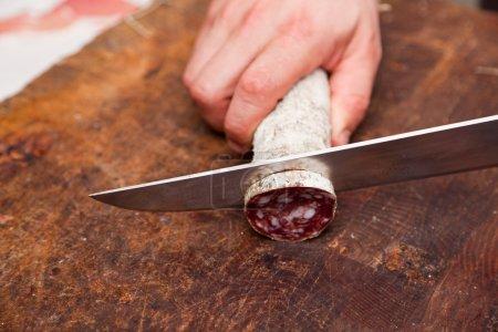 Butcher Slicing Salami